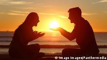 Paar sitzt am Strand bei Sonnenuntergang
