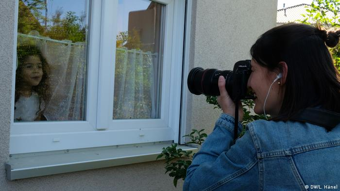 Photographer Theresa Rooney taking pictures of a girl behind a window