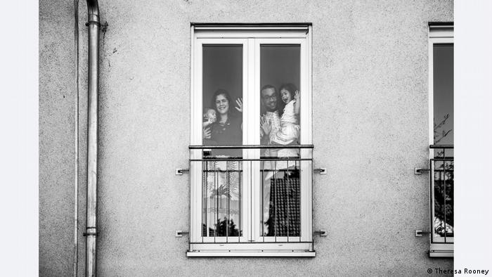 A family of four waves through a window for a photograph