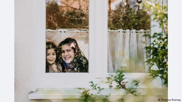 Two girls on the other side of a window