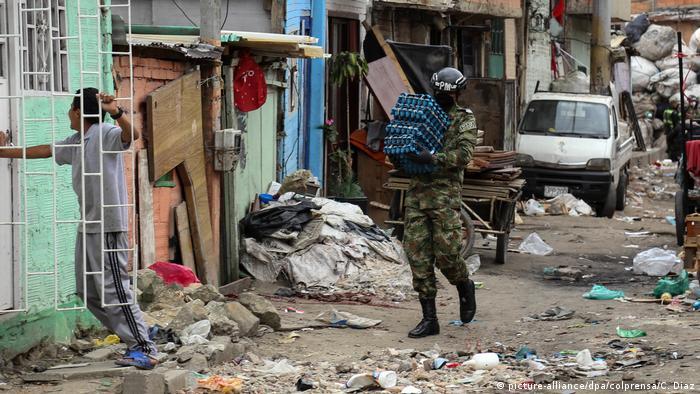 Soldado carrega caixas de ovos em uma rua com muito lixo.