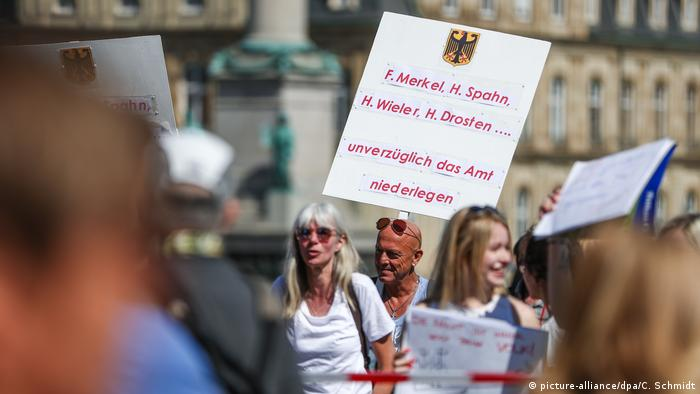 A protester holds a sign demanding that Angela Merkel, Christian Drosten and others resign