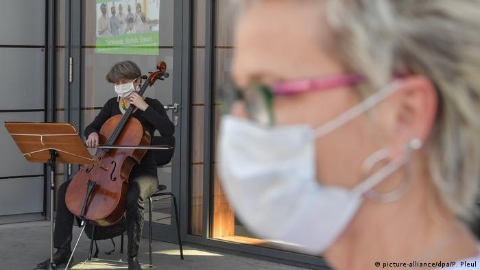 Mulher de máscara e músico de máscara ao fundo