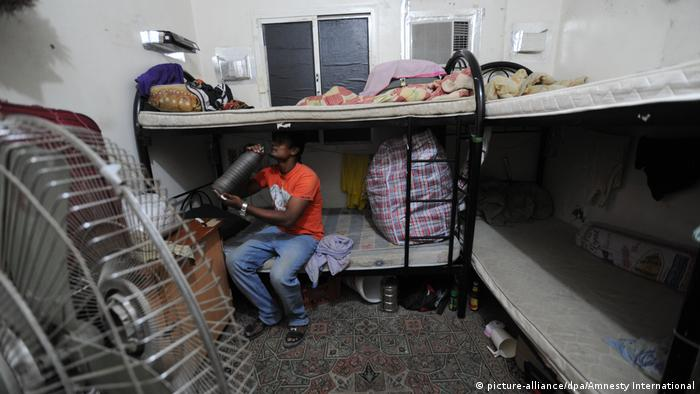 A migrant worker sits on a bed in a small room in a labor camp in Qatar