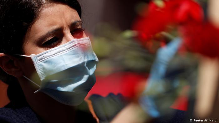 Italien   Coronavirus: Frau mit Mundschutz arrangiert Blumen zum Tag der Befreiung Italiens