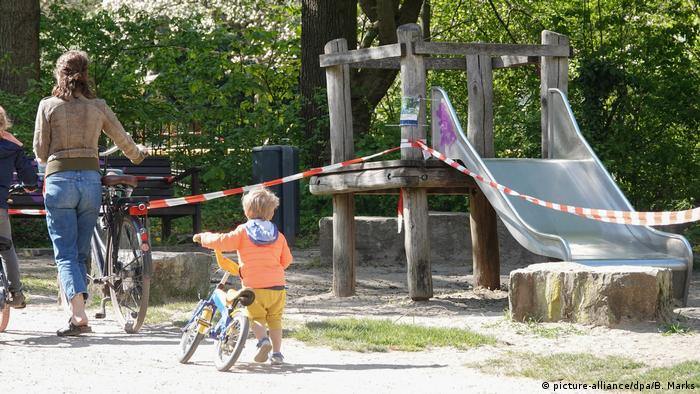 A child and and adult pushing bikes past a playground in Hamburg