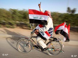 An Iraqi man on a bicycle covered with Iraqi flags displays his inked finger after casting his vote for the parliamentary election, in Najaf, Iraq, Sunday, March 7, 2010.