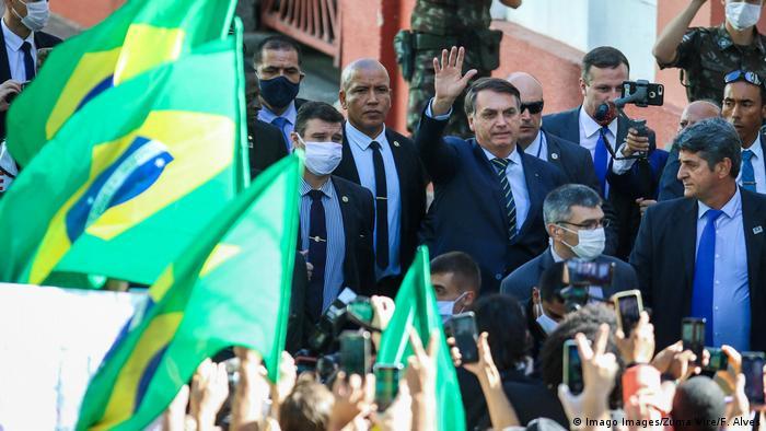 O presidente brasileiro Jair Bolsonaro em visita a Porto Alegre para nomeação de novo chefe de QG na cidade. À frente da foto, bandeiras do Brasil, ladeadas por apoiadores de Bolsonaro, que acena para eles enquanto é fotografado e filmado pelos celulares.