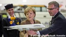 ARCHIV - 18.11.2015, Hessen, Frankfurt/Main: Bundeskanzlerin Angela Merkel (CDU) besucht die Lufthansa. Dabei nimmt Sie zusammen mit Lufthansa-Chef Carsten Spohr das Modell eines Airbus A380-800 in die Hand. Zu Staatshilfen für die schwer gebeutelte Lufthansa ist Anfang der kommenden Woche ein Krisengespräch auf höchster Ebene geplant. Wie die Deutsche Presse-Agentur am Samstag (25.04.2020) erfuhr, wollen unter anderen Kanzlerin Angela Merkel (CDU) und Finanzminister Scholz (SPD) mit Lufthansa-Chef Spohr über ein Rettungspaket verhandeln. Foto: picture alliance / dpa +++ dpa-Bildfunk +++ | Verwendung weltweit