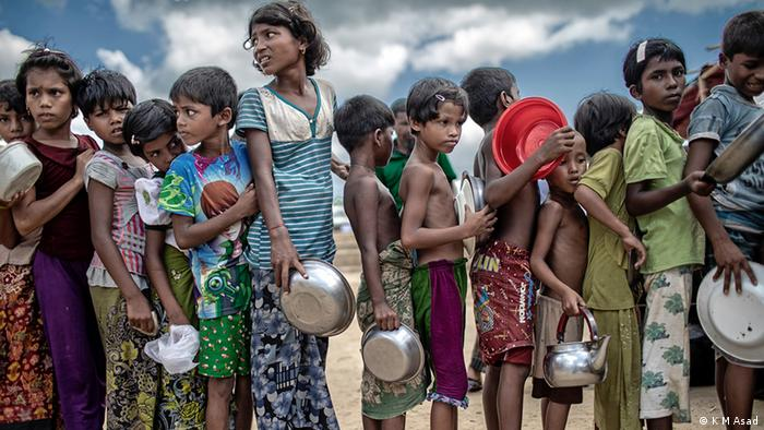 Rohingya refugee children queue for food in a camp in Cox's Bazar, Bangladesh