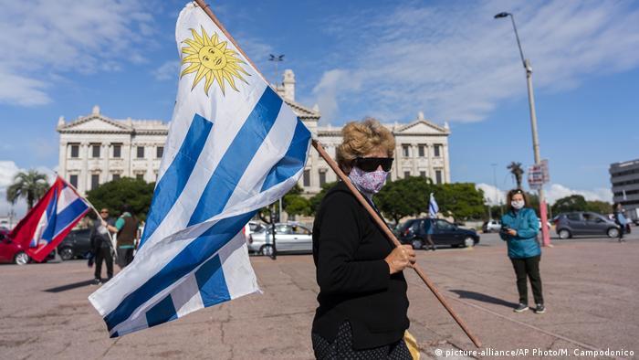 Mulher de máscara com a bandeira do Uruguai sobre o ombro anda numa praça