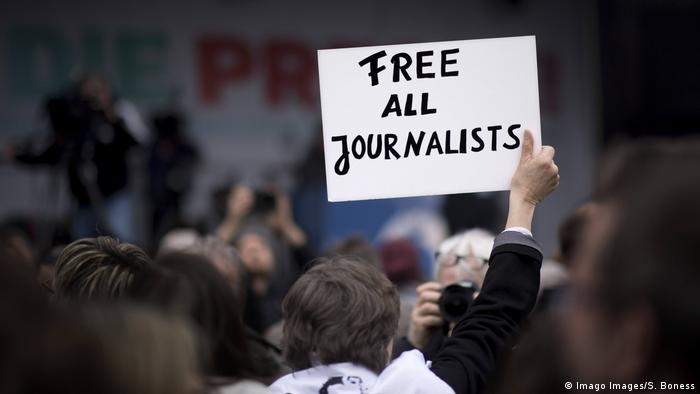 A person holding a sign that reads Free all journalists