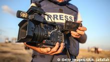 Ein Journalist in schusssicherer Weste hält eine beschädigte Kamera ins Bild.