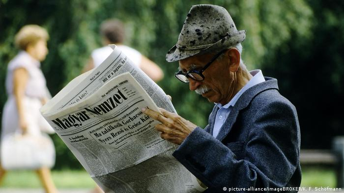 An elderly man reads a Hungarian newspaper in the park