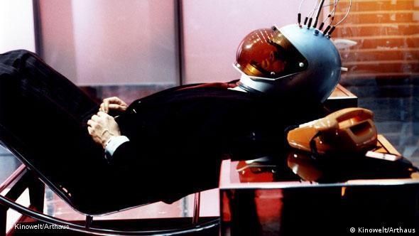 Mann liegend auf Stuhl mit Helm - Szene aus dem Film Welt am Draht von Rainer Werner Fassbinder