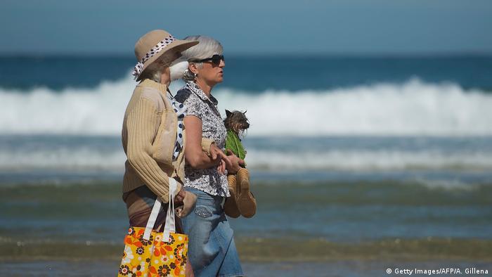 بعد تخفيف قيود الحجر الصحي في اسبانيا سيدتان تقومان بجولة على الشاطئ في سان سيباستيان