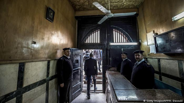 A brown walled corridor leads past three men in uniform during a guided tour of Egypt's Tora prison