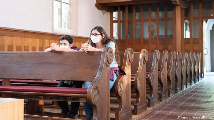 A church with just two people sat in it amongst empty pews