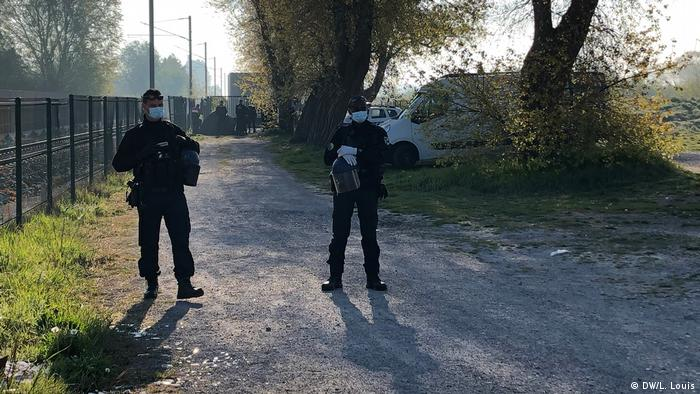Police block the entrance to a refugee camp in Calais