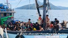 In this handout photo released on Sunday, April 5, 2020 by the Malaysian Maritime Enforcement Agency, a wooden boat carries suspected Rohingya migrants detained in Malaysian territorial waters off the island of Langkawi, Malaysia. Malaysian authorities said they have arrested a boatload of 202 people believed to be minority Muslim Rohingya refugees after their boat was found adrift Sunday morning near the northern resort island of Langkawi. (Malaysian Maritime Enforcement Agency via AP) |