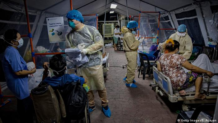 Medical personnel wearing protective clothing work to treat patients