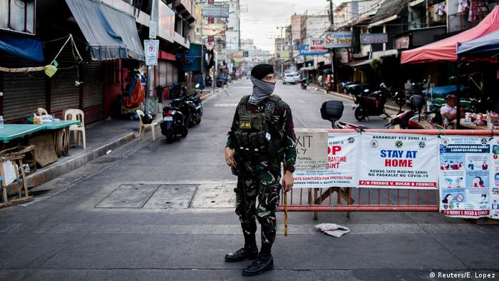 A soldier wearing a face mask holds on his weapon as he guards an empty street following the lockdown imposed to contain the coronavirus disease (COVID-19) in Manila