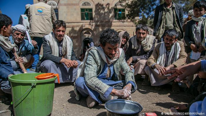 A man scrubs his hands near a pot of water (UNICEF/UNI324899/AlGhabri)