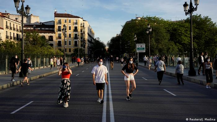People walk and exercise on a street in Madrid, Spain.