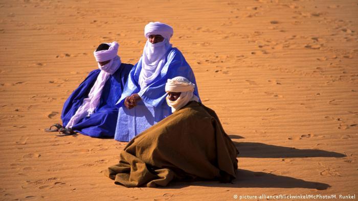 Drei Tuareg sitzen in langen Gewändern mit Kopfbedeckungen und Gesichtsschleiern auf Sand (picture-alliance/blickwinkel/McPhoto/M. Runkel)