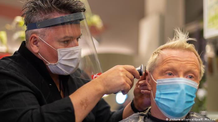 A visor-wearing hair dresser gives a haircut to a masked customer (picture-alliance/dpa/R. Michael)