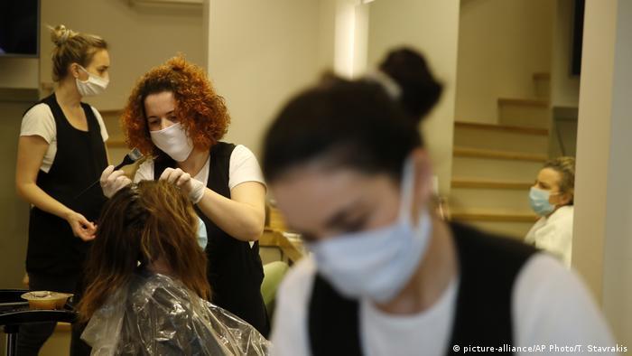 Penata rambut sedang mewarnai rambut konsumen di sebuah Salon di Athens, Yunani.