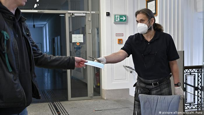 A teacher hands a face mask to a pupil before lessons begin at a high school in Vienna, Austria.