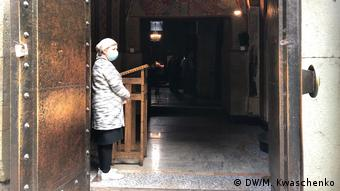 На входе в церковь стоит женщина в маске
