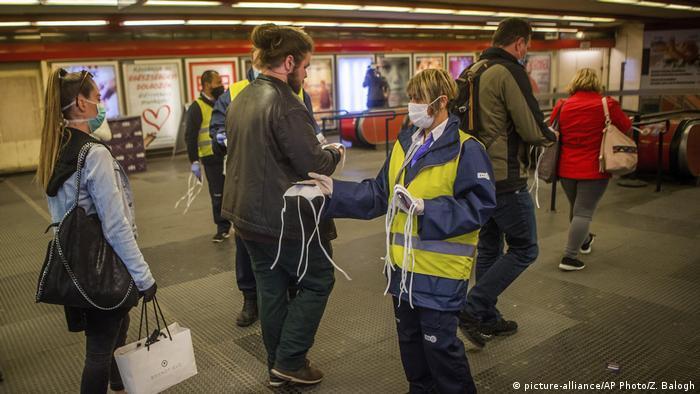 Seorang pekerja transportasi membagikan masker kepada masyarakat yang sedang berpergian di Lapangan Nyugati di Budapest, Hungaria.