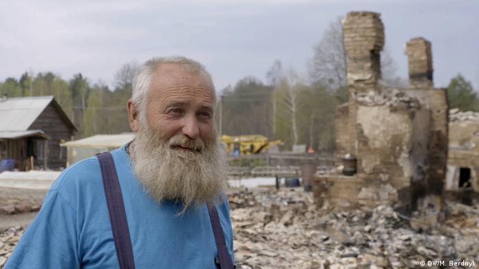 Местный житель на фоне сгоревшего дома.