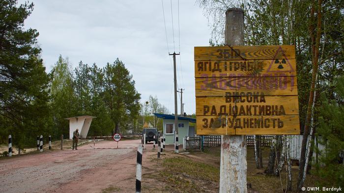 Блок-пост на пути в Личманы и табличка, предупреждающая о радиоактивном загрязнении.