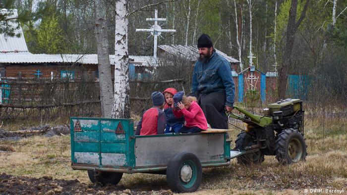 Местный житель везет детей на прицепе к самоходному плугу