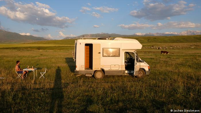 Camper van parked in the middle of fields at dusk