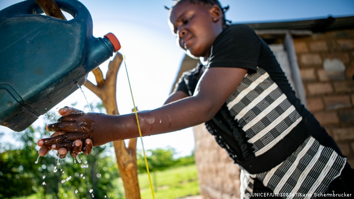 A girl washes her hands beneath a faucet made from an old plastic container (UNICEF/UNI308267/Karin Schermbrucker)