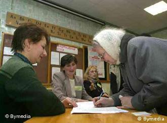 Женщина получает бюллетень на избирательном участке