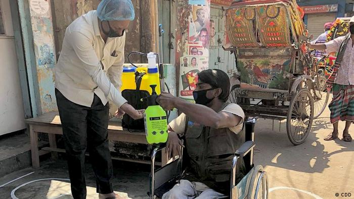 A man in a wheel chair dispenses disinfectant to his community (CBM / CDD)