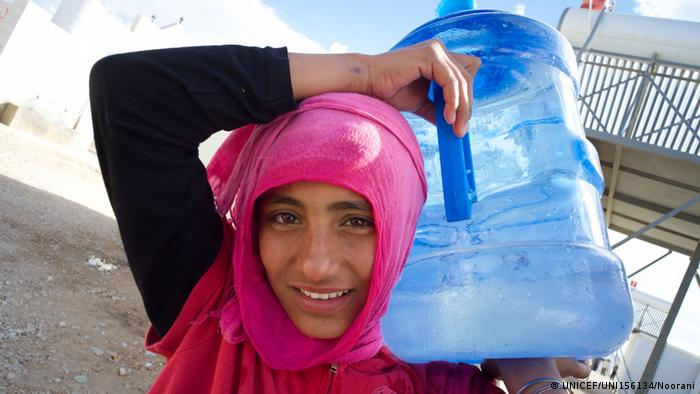 A teenage girl carries a plastic jug of water on her left shoulder (UNICEF/UNI156134/Noorani)