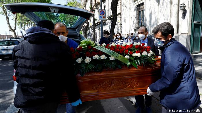 Pallbearers carry a coffin from a hearse while wearing face masks in Catalina, Italy.