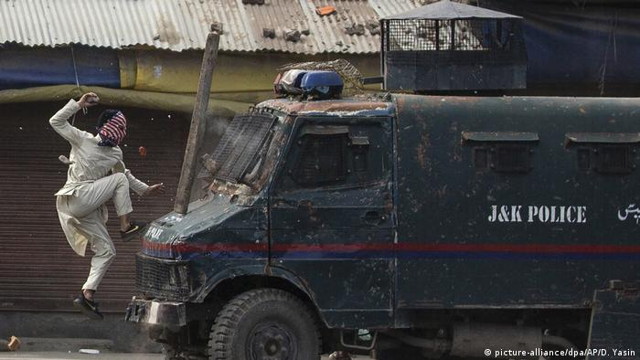 A masked demonstrator jumps onto the hood of an armored vehicle