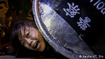 A woman cries out in pain underneath a police shield (Reuters/T. Siu)