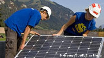Young people installing solar panels on a rooftop