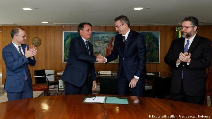 Brasilein Präsident Jair Bolsonaro gibt Rolando Alexandre de Souza die Hand