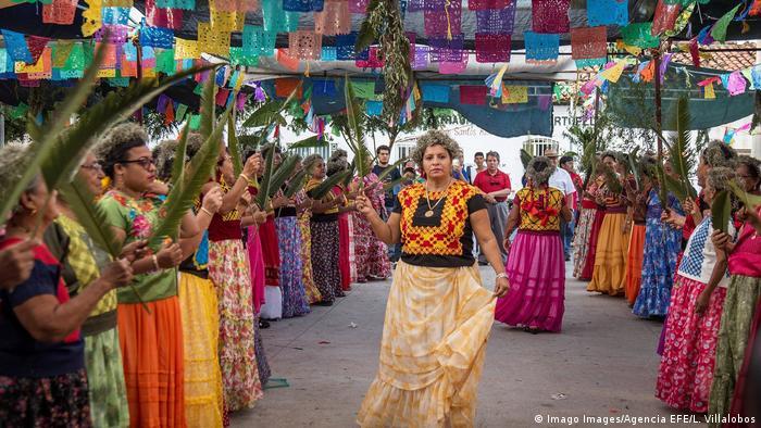 Indígenas mexicanos vestidos con coloridas ropas tradicionales celebrando un festival agrícola.