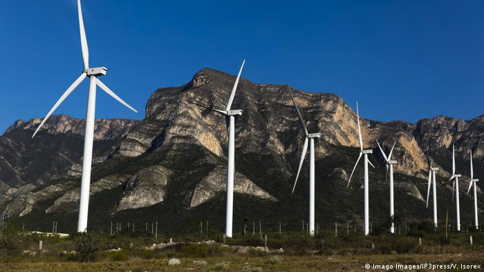 A row of wind turbines against a rocky background
