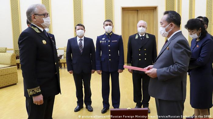 In this photo released by Russian Embassy in the DPRK/Russian Foreign Ministry Press Service on Tuesday, May 5, 2020, Russian Ambassador to Democratic People's Republic of Korea Alexander Matsegora, left, and Democratic People's Republic of Korea Foreign Minister Ri Son-gwon, foreground right, both wearing face masks to protect against coronavirus, attend a ceremony of awarding North Korean leader Kim Jong-un with Russia's 75th anniversary Victory medal for his major contribution in commemorating Soviet soldiers, who died in 1945 during Korea's liberation, at the Mansudae Palace of Congress in Pyongyang, North Korea. (picture-alliance/AP/Russian Foreign Ministry Press Service/Russian Embassy in the DPRK)